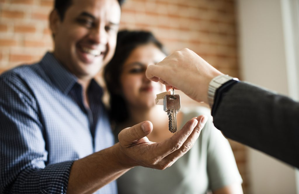 Image: man handing keys to smiling couple
